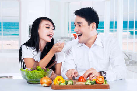 family together: Portrait of happy young couple preparing healthy food with fresh vegetables in the kitchen Stock Photo