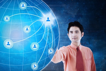 Concept of social network connection. Young Asian businessman pressing social network icon and globe on the virtual screen Stock Photo