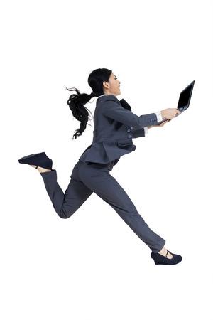 tecnología informatica: Empresaria joven que se ejecuta en el estudio mientras que lleva un ordenador portátil, aislado en fondo blanco