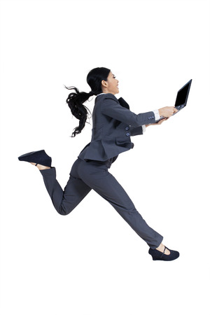 haste: Young businesswoman running in the studio while carrying a laptop computer, isolated on white background