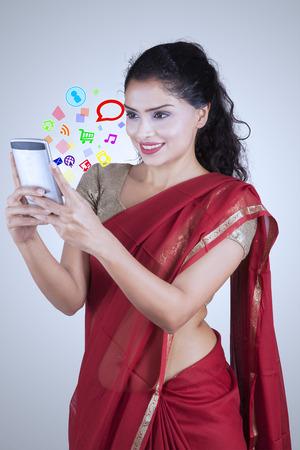 mujeres fashion: mujer india hermosa que desgasta la ropa saree durante el uso de teléfonos inteligentes con el icono de los medios sociales