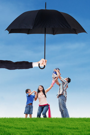 protection plan: Portrait of happy family playing and jumping together on the park under umbrella. Life and family insurance concept Stock Photo