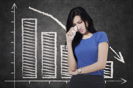 declining: Concept of bankruptcy. Sad businesswoman crying in front of declining graph on the blackboard