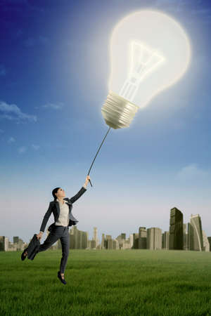 light worker: Photo of a young female worker flying on the meadow with bright light bulb, shot outdoors