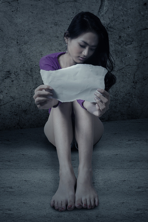 prostitution: Photo of a depressed teenage girl showing empty paper while sitting on the floor