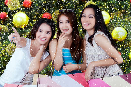 young tree: Three beautiful girls holding shopping bags and pointing at something, shot with christmas decoration background