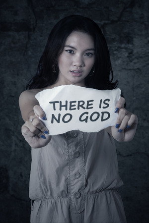 atheist: Picture of atheist teenage girl holding a paper with text THERE IS NO GOD Stock Photo