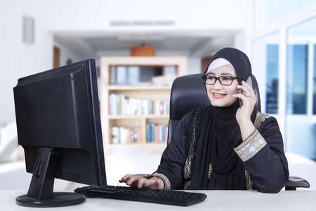 home business: Arabic businesswoman wearing headscarf talking on the cellphone while working at home