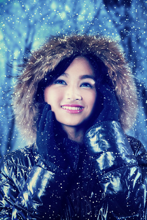 fur hood: Portrait of a beautiful young girl smiling and wearing jacket with fur hood in winter forest