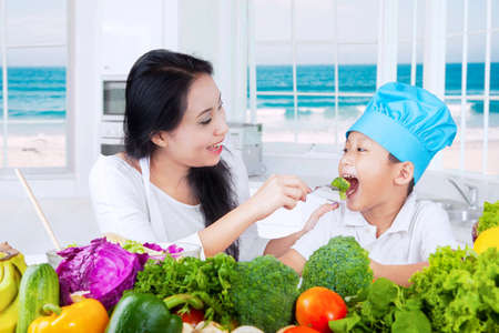 asia children: Young mother feeding her son with fresh vegetables in the kitchen at home