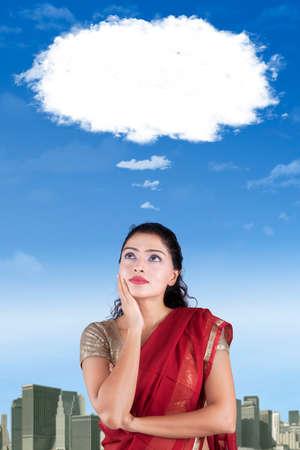 persona pensando: mujer india reflexivo usando ropa saree y mirando a la burbuja del discurso nube Foto de archivo