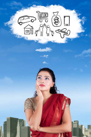 imagines: Indian woman wearing saree clothes and imagines her wish on the cloud speech bubble Stock Photo