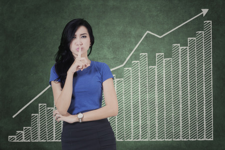 Young businesswoman showing silence gesture in front of growing financial graph