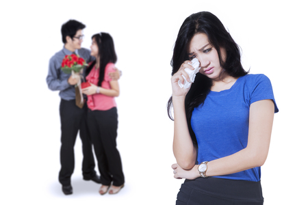 Betrayal Konzept. Sad Frau vor der jungen Paar zu weinen auf dem Rücken stehend, isoliert auf weißem Hintergrund Standard-Bild