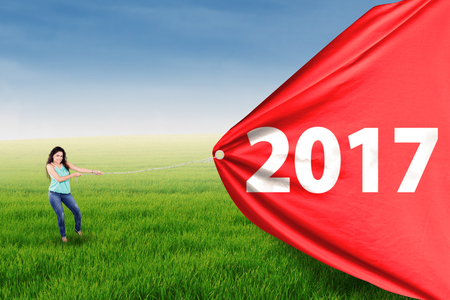 Asian young woman is pulling big red flag with 2017 on the meadow Stock Photo