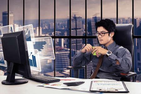 hombres trabajando: Foto de un empresario de sexo masculino que trabaja en la oficina mientras disfruta de una taza de café con el gráfico virtual en la pantalla del ordenador