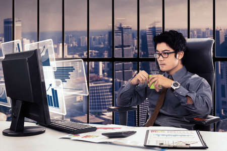 asian guy: Photo of a male entrepreneur working in the office while enjoying a cup of coffee with virtual graph on the computer monitor