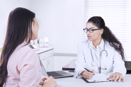 preguntando: Image of doctor looking at the computer and holding pen with clipboard on the desk while listening consultation from her patient in the doctors office