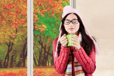 beautiful weather: Beautiful woman wearing hat and knitted standing by the window with a cup of hot chocolate, autumn weather in the window