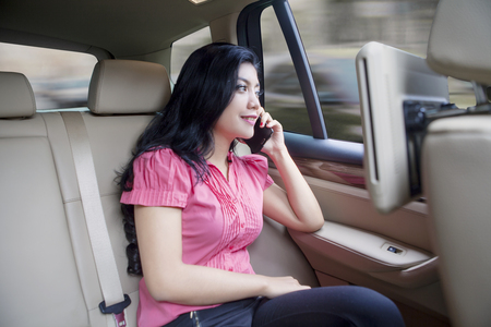 driving a car: Beautiful asian young woman sitting and using cellular in a car as passenger, looking at car window in the morning