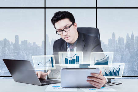 using the computer: Young Arabian businessman looks busy, working in the office with laptop and virtual financial statistic on digital tablet Stock Photo