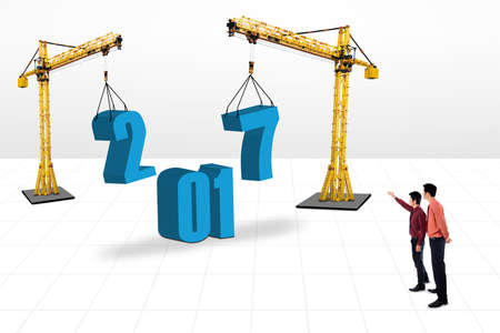 new construction: Two businessmen looking at the numbers 2017 under construction. Isolated on white background