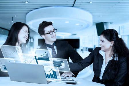 jovenes emprendedores: Tres jóvenes empresarios con el gráfico financiero virtual en el ordenador portátil, estrechando la mano en una reunión de negocios