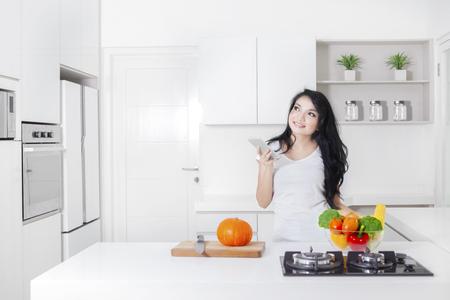 Jonge vrouw koken in de keuken terwijl een mobiele telefoon en denk idee Stockfoto