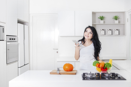 Young woman cooking in the kitchen while holding a mobile phone and thinking idea