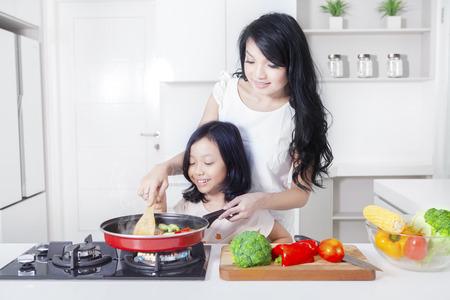 Retrato de una mujer bonita y su hija de verduras para cocinar con una fritura en la cocina Foto de archivo - 63532412