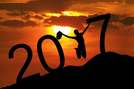 Image of happy woman jumping on the hill at the sunset time, celebrating new year of 2017 Stock Photo