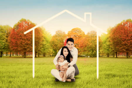 parejas de jovenes: Father hugging mother and holding his baby in arms with smiling at the camera while sitting under a house symbol on the park