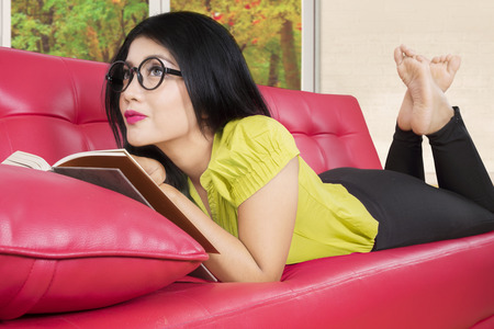 woman laying: Image of beautiful woman daydreaming on the living room with book on the red couch, autumn on the window
