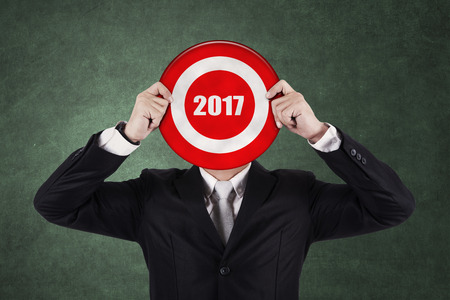 bull's eye: Businessman with a dart in bulls eye with number 2017, Isolated on green background Stock Photo
