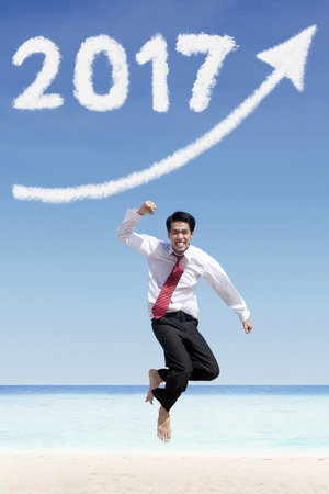 financial year: Male jumping at beach, under increase arrow sign and number 2017 cloud