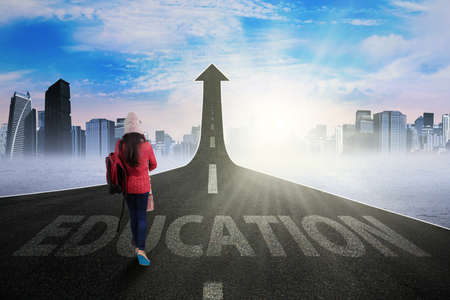 higher education: Young student wearing warm clothes and walking on the highway turning into upward arrow  to gain higher education
