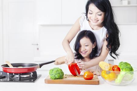 Portret szczęśliwa matka i córka gotowania razem w kuchni podczas cięcia warzyw