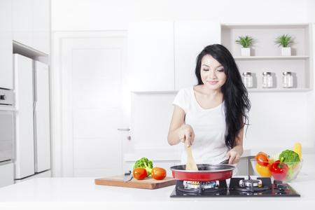 Portrait d'une belle femme de cuisson de légumes sur la cuisinière avec la friture, une balle dans la cuisine à la maison