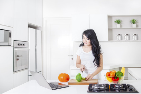 Beautiful woman cooking in the kitchen while following recipe on the laptop