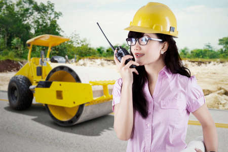 walkie talkie: Beautiful contractor talking on the walkie talkie with a backhoe on the background, shot outdoors