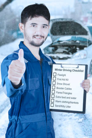 tip up: Male mechanic showing thumb up while holding clipboard with list of winter driving tips