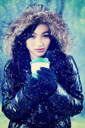 fur hood: Young girl holding hot coffee with disposable cup and wearing winter jacket with fur hood Stock Photo