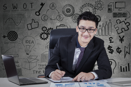 hombre arabe: Portrait of a young arabian businessman wearing formal suit and writing on the clipboard while smiling at the camera with business doodles on the wall