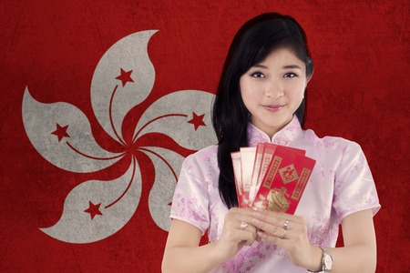 celebrate year: Chinese girl wearing cheongsam dress and celebrate Chinese new year while holding envelope with flag of Hong Kong Stock Photo