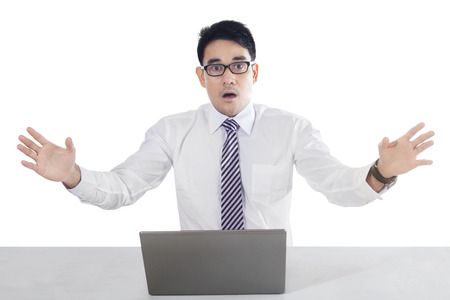 white man: Businessman sitting in front of laptop with shocked by something, isolated on the white background Stock Photo