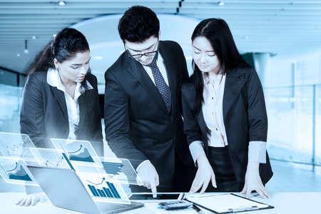 jovenes emprendedores: Tres jóvenes empresarios discutiendo en la oficina mientras mira la tabla en la tableta con estadísticas financieras virtuales en el ordenador portátil