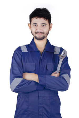 service man: Portrait of a young Arabian mechanic smiling at the camera while wearing uniform and holding a wrench