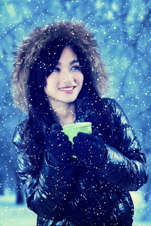 warm clothing: Asian girl wearing winter clothing and drinking hot coffee to warm up in snowy day