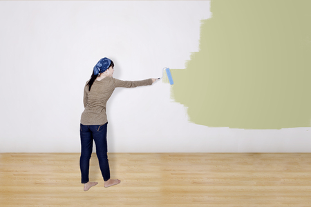 wall paint: Girl painting on white wall with cream color paint