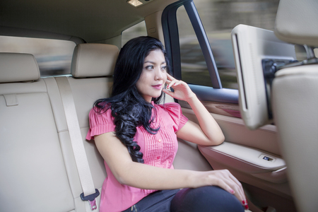 rich people: Potrait of young woman sitting on a car backseat and  looking through car window on the road